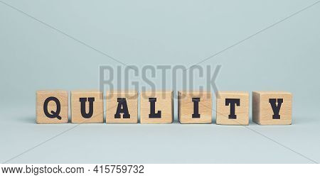 The Word Quality Made From Wooden Cubes On Blue Background. Conceptual Photo