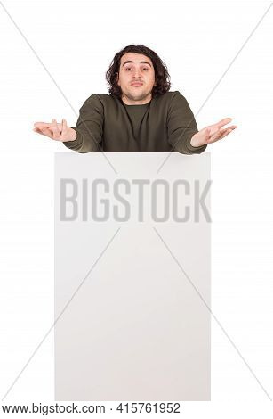 Perplexed And Confused Man, Stands Behind A Blank Banner, Hands Raised Outstretched, Shrugging Shoul