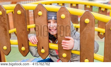 Little smiling girl peeping through a wooden fence on playground