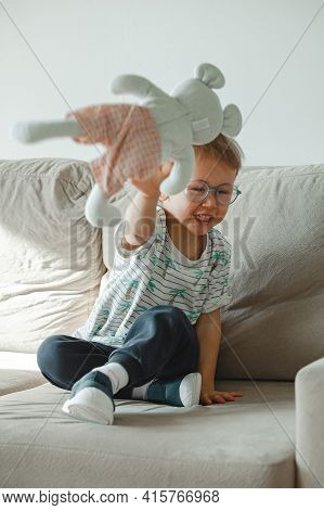 A Child With Autism In Glasses Sits On The Sofa And Is Sad, Angry And Throws A Soft Toy Mouse
