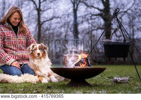 Tricolor Australian Shepherd Sits Next To A Young Woman By The Campfire. In Winter, Snow On The Gras