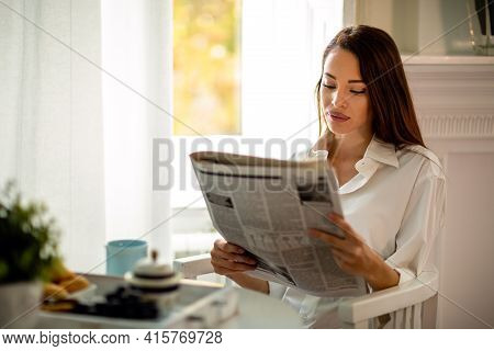 Young Woman Reading Newspaper While Having Morning Coffee At Home