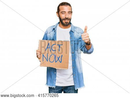 Attractive man with long hair and beard holding act now banner smiling happy and positive, thumb up doing excellent and approval sign