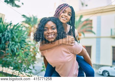 Beautiful african american mother giving daughter piggyback ride smiling happy at the park.