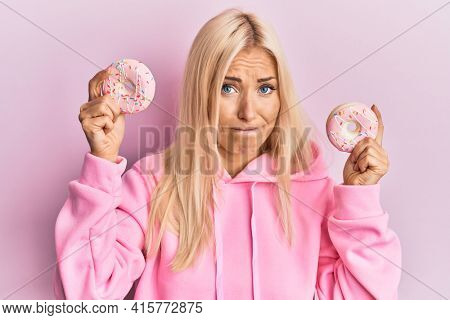 Young blonde woman holding tasty pink doughnuts over eyes skeptic and nervous, frowning upset because of problem. negative person.