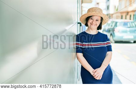 Beautiful brunette woman with down syndrome at the town on a sunny day wearing summer hat leaning on the wall