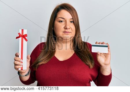 Beautiful brunette plus size woman holding gift and credit card relaxed with serious expression on face. simple and natural looking at the camera.