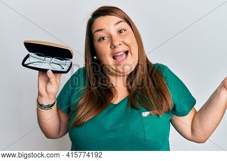 Beautiful brunette plus size woman holding glasses in eyewear case celebrating achievement with happy smile and winner expression with raised hand