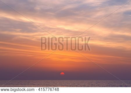 Sun Goes Down To The Sea Horizon. Bright Cloudy Sunset Above The Seascape. Photo With Soft Focus.