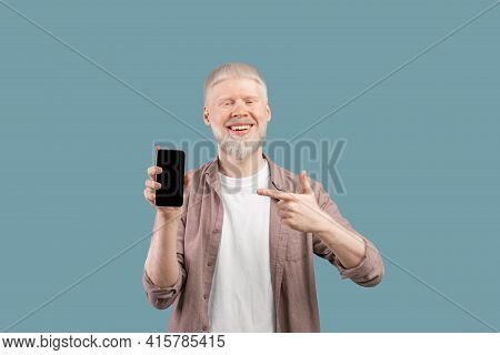 Check This App. Joyful Albino Guy Holding And Pointing Finger At Smartphone With Black Screen, Studi