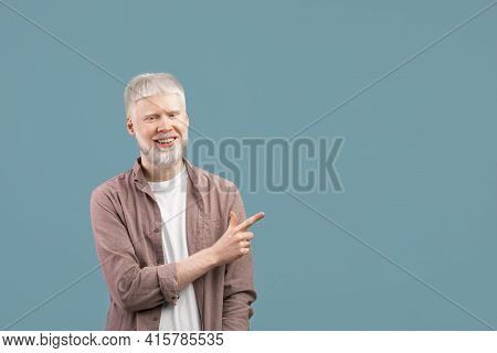 Cool Offer. Confident Albino Man Pointing At Free Space On Turquoise Studio Background And Smiling T