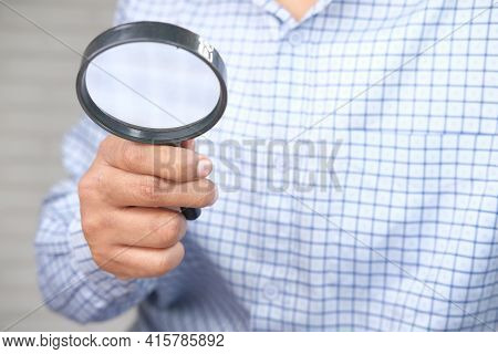 Young Man Discovering His Luck With Magnifying Glass