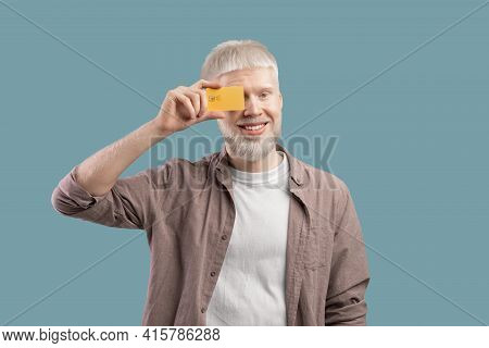 Happy Albino Man Holding Credit Card In Front Of His Eye On Turquoise Studio Background