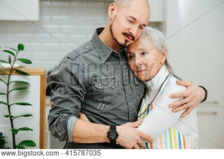 Immersed Granny Hugging Her Son, Leaning On His Chest, Feeling The Moment