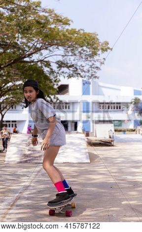 Little Asian Girl Play Surf Skate Board At Park Skate Ramp Outdoors On Morning. Happy Girl Play Surf