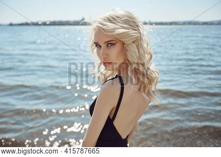 Beautiful Portrait Of A Blonde Woman By The Lake In A Black Tight Dress. Perfect Hair Styling, Curly