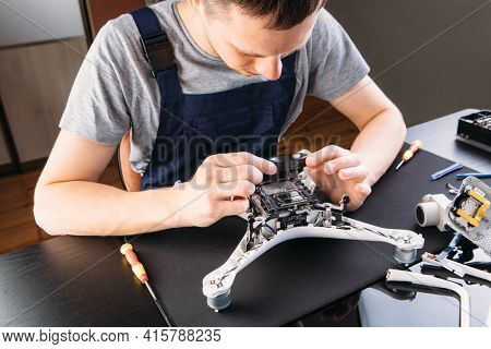 Close-up Of Person's Hand Repairing Drone Using Screwdriver. a man working in a repair shop