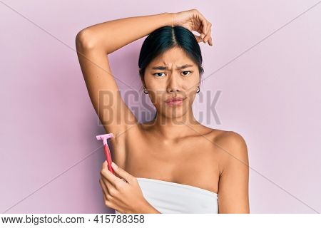 Young chinese woman wearing shower towel using razor skeptic and nervous, frowning upset because of problem. negative person.