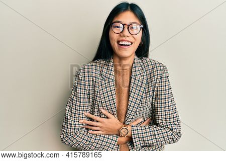 Young chinese woman wearing business style and glasses smiling and laughing hard out loud because funny crazy joke with hands on body.