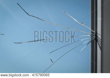 Cracked Glass In The Window Frame Of The House. Damaged Window As A Consequence Of Vandalism Or Natu