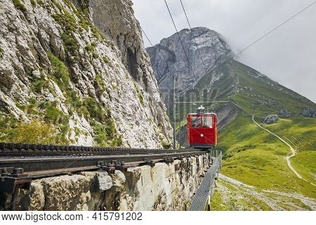 Cogwheel Train Passing Mountain Landscape Of Swiss Alps.red Train On Cog Railway Between Mount Pilat