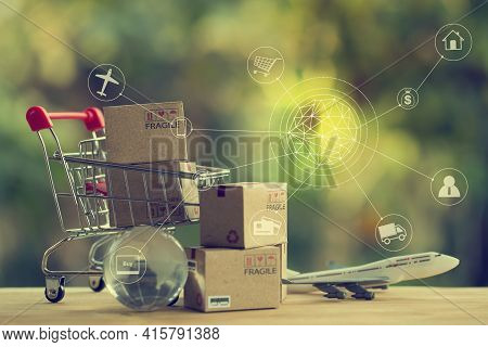 Shopping Online And E-commerce Concept: Paper Boxes In A Shopping Cart And Crystal Globe, Plane. Onl