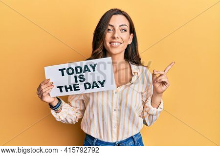 Young brunette woman holding today is the day smiling happy pointing with hand and finger to the side