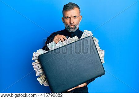 Middle age handsome man holding briefcase full of dollars skeptic and nervous, frowning upset because of problem. negative person.