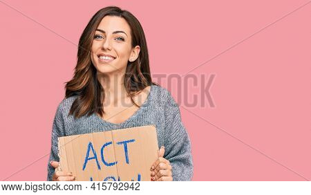 Young brunette woman holding act now banner looking positive and happy standing and smiling with a confident smile showing teeth