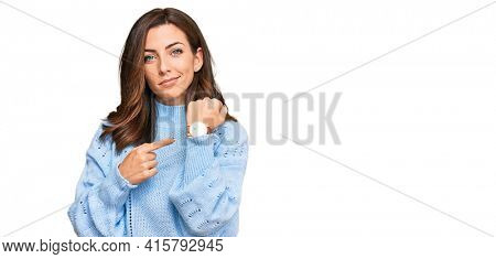 Young brunette woman wearing casual winter sweater in hurry pointing to watch time, impatience, looking at the camera with relaxed expression