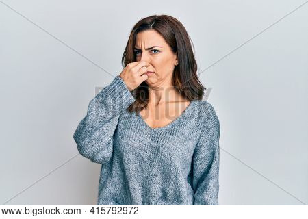 Young brunette woman wearing casual winter sweater smelling something stinky and disgusting, intolerable smell, holding breath with fingers on nose. bad smell