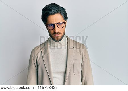 Young hispanic man wearing business jacket and glasses skeptic and nervous, frowning upset because of problem. negative person.