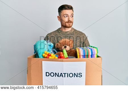 Young redhead man holding donation box with toys smiling looking to the side and staring away thinking.