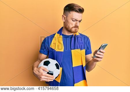 Young redhead man wearing hooligan scarf and using smartphone depressed and worry for distress, crying angry and afraid. sad expression.