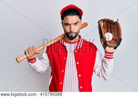 Young man with beard playing baseball holding bat and ball skeptic and nervous, frowning upset because of problem. negative person.