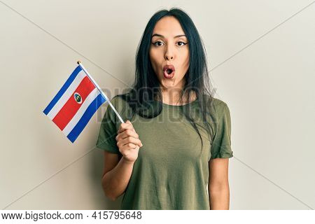 Young hispanic girl holding costa rica flag scared and amazed with open mouth for surprise, disbelief face