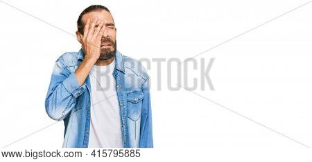 Attractive man with long hair and beard wearing casual denim jacket yawning tired covering half face, eye and mouth with hand. face hurts in pain.