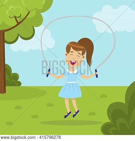 Cute Smiling Girl Jumping Rope In The Park. Happy Jumping Kid. Child Enjoying Exercising Outside. Ha