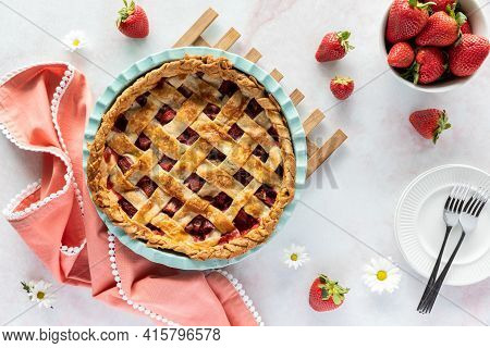 Top Down View Of A Lattice Topped Strawberry Rhubarb Pie Fresh Out Of The Oven, Cooling On A Wooden