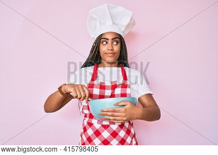 Young african american woman with braids cooking using baker whisk smiling looking to the side and staring away thinking.