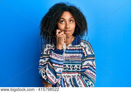 Beautiful african american woman with afro hair wearing casual clothes thinking concentrated about doubt with finger on chin and looking up wondering