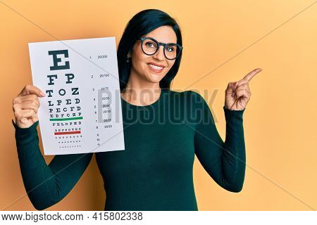 Young caucasian woman holding optometry glasses and eyesight test smiling happy pointing with hand and finger to the side