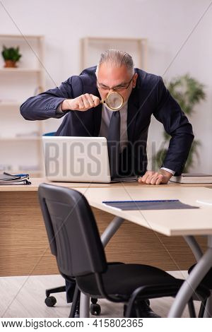 Old male employer sitting in the office