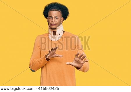 African american man with afro hair wearing cervical neck collar disgusted expression, displeased and fearful doing disgust face because aversion reaction. with hands raised