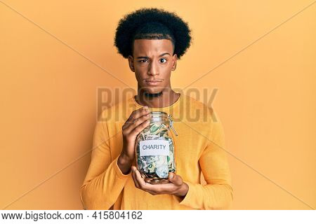 African american man with afro hair holding charity jar with money skeptic and nervous, frowning upset because of problem. negative person.