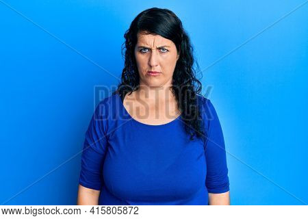 Plus size brunette woman wearing casual blue shirt skeptic and nervous, frowning upset because of problem. negative person.