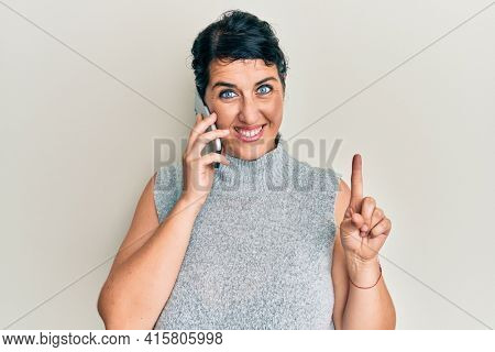 Plus size brunette woman having conversation talking on the smartphone smiling with an idea or question pointing finger with happy face, number one