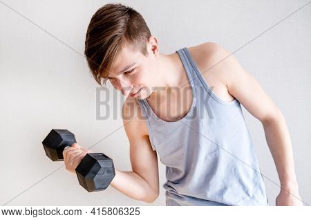 Young Man In Hold A Heavy Dumbbell By The White Wall