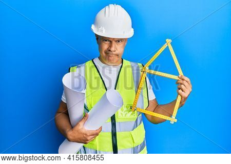 Middle age bald man wearing architect hardhat holding build project skeptic and nervous, frowning upset because of problem. negative person.