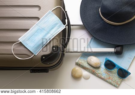 Travel During The Time Of Covid-19. Medical Mask, Suitcase, Sun Glasses, Map, Seashells On The White